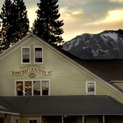 Front of old Western-style mercantile building backed by snow-capped mountains and tall pines.