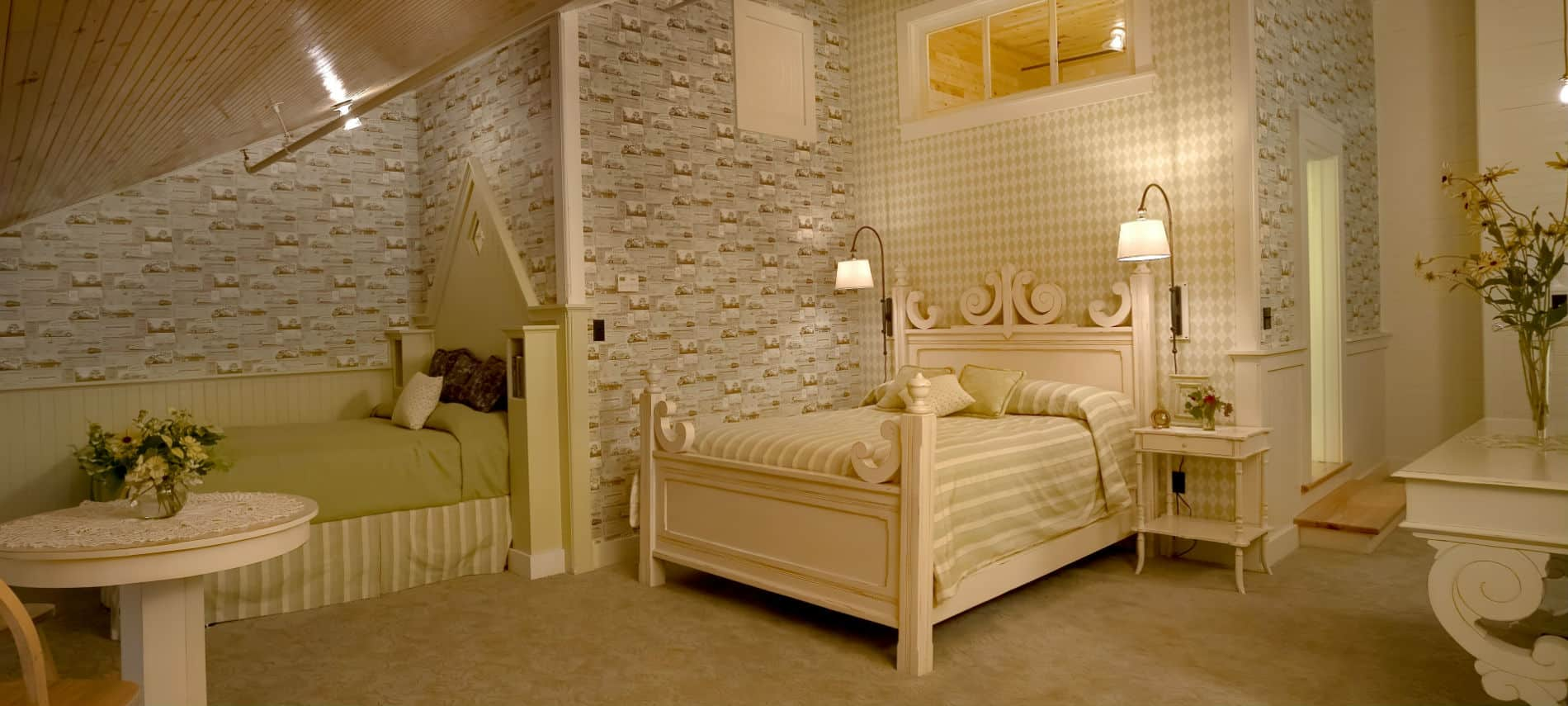 Bedroom with patterned wallpaper and all cream colored furniture holds a queen bed and a twin bed.