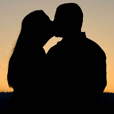 Silhouette of a man and woman embracing in the dusk of sunset.