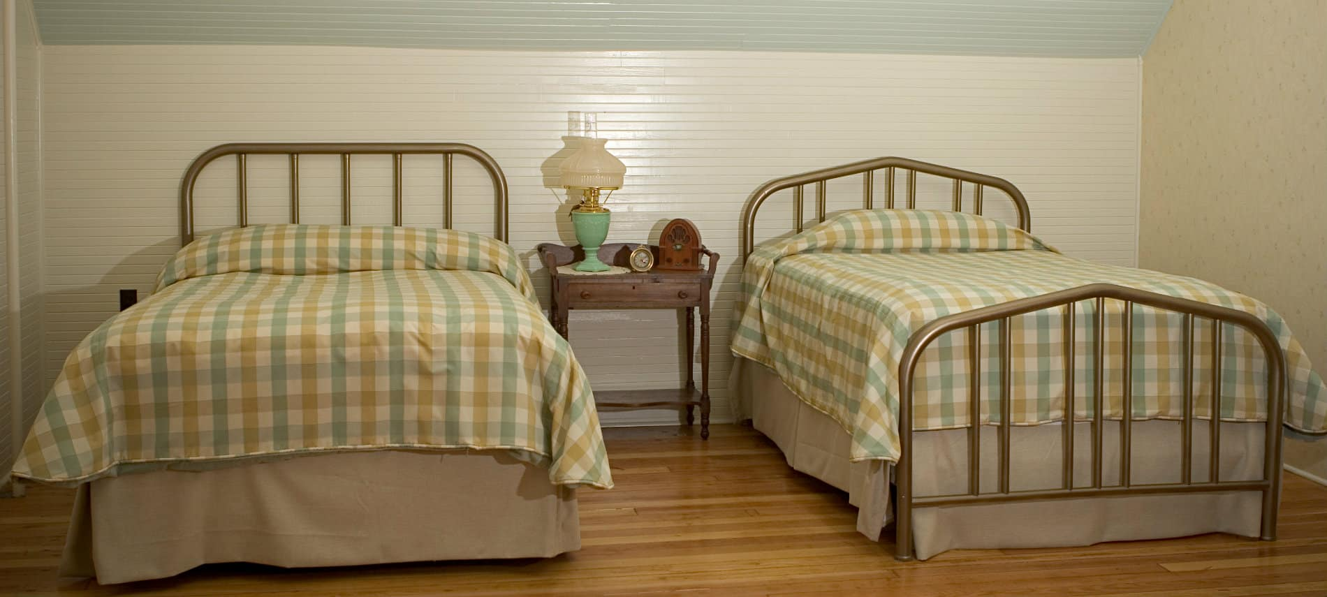 Twinn brass beds made up in white tan and cream plaid bedding in a bedroom with white paneling.