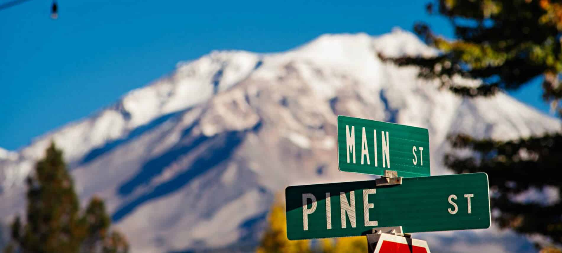 Street signs reading Main St and Pine St backed by snow-capped mountains.