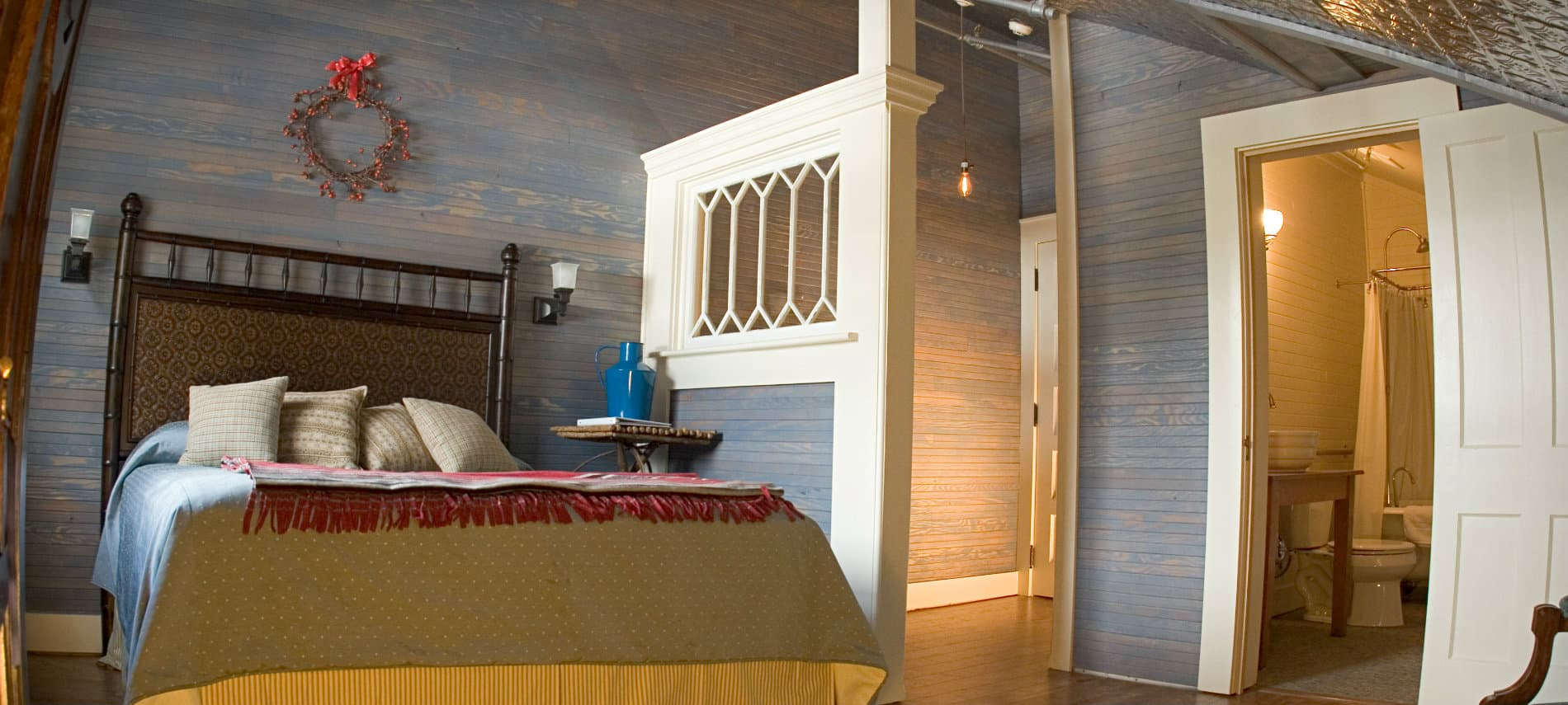 Unique pitched roof bedroom with blue wash wooden paneling and a bed set into an alcove next to a window.