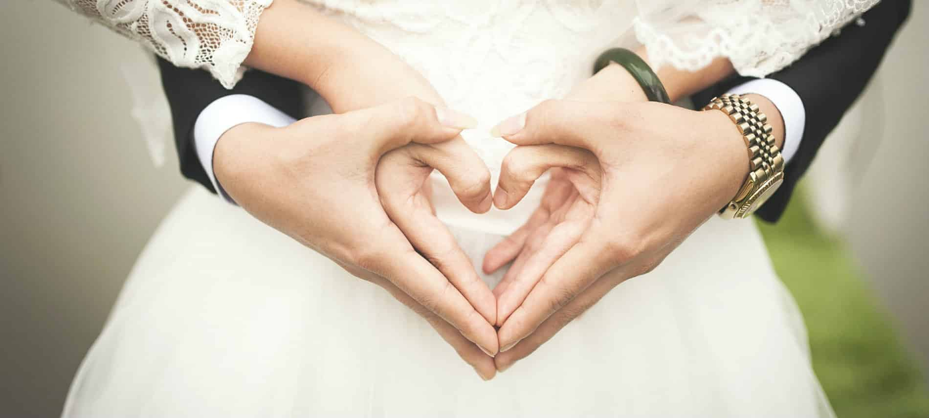 Bride and groom's hands held together in a heart-shape.