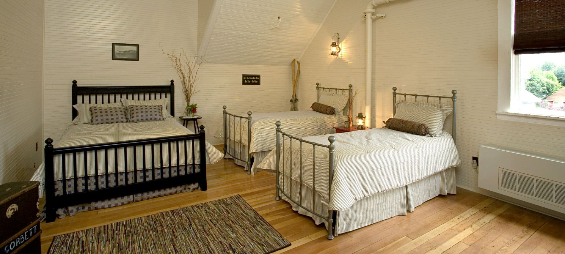 Large suite with a queen and two twin beds made up in white with wooden floors and red and white walls.