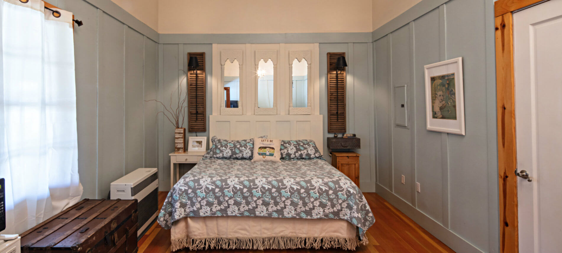 Large bed made up in a blue and grey patterned spread with a white wood and mirror headboard in bedroom with blue wainscoting.
