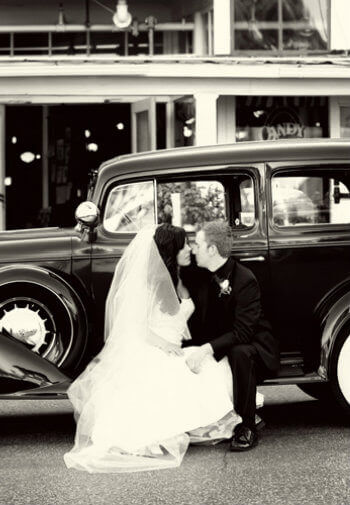 Bride and groom kissing on the sideboard of an antique black car.