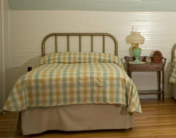 Brass bed made up in blue and tan covers next to a side table in a room with white wood paneling.