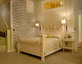 Bedroom decorated in cream carpet, furniture, bedding, and patterned wallpaper, with tall ceilings.