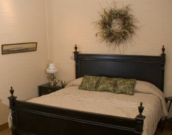 King sized bed with a wooden headboard made up in cream in a bedroom with cream paneling.