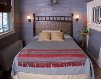 Bed with wooden headboard made up in blue and red in a paneled room with a large window.