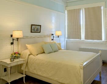 Light and airy bedroom with a queen bed made up in white and bedside tables with lamps.