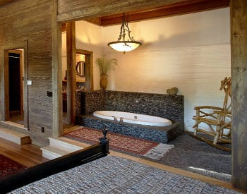 Rustic chic bedroom with a sitting area and a free standing tub in an alcove.