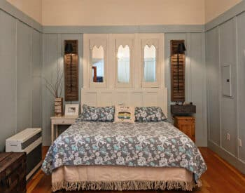 Large bed made up in a blue and grey patterned spread with a white wood and mirror headboard.