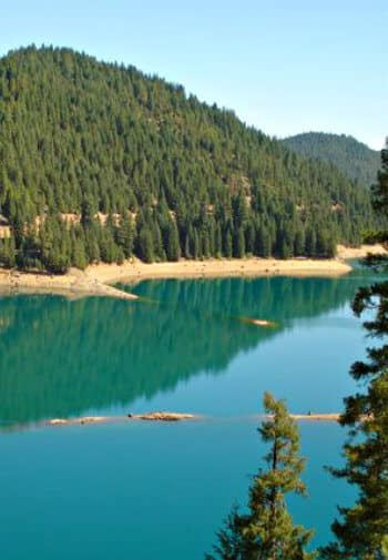 Large blue water lake surrounded by hills covered with pine trees.