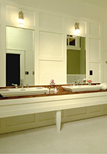 Two large white sinks set into a wooden vanity in a white bathroom with a white penny-tile floor.