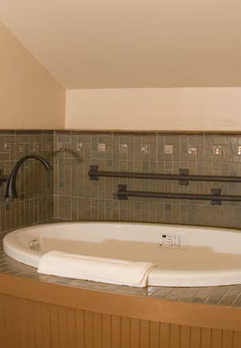Big soaking tub set into an alcove with under lighting and bronze faucets and grab bars.