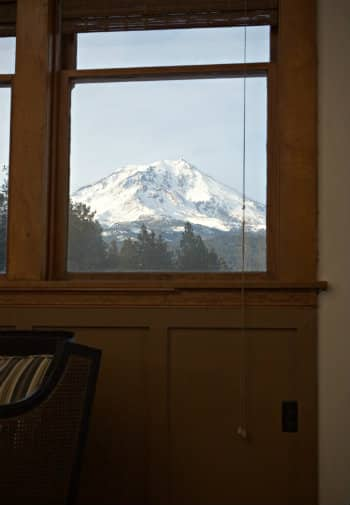 View of snow-capped mountain from within a bedroom window.