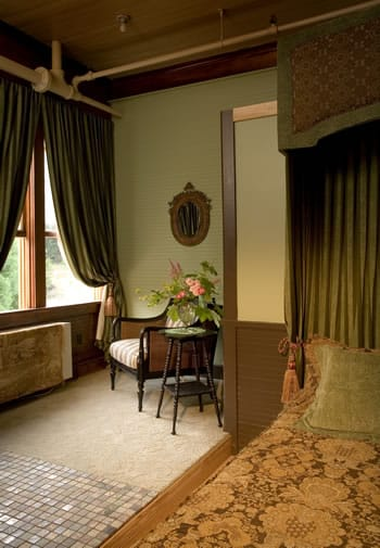 Elegant and serene bedroom holds abed with a framed headboard and a chair that faces out to a large window.