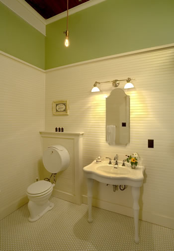 Old fashioned stool and white vanity in a bathroom with cream paneling and white tile floor.