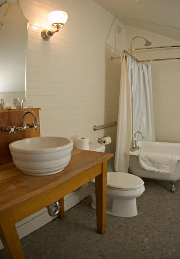 Adorable bathroom with a shower in the clawfoot tub, a wooden vanity with a white bowl sink and tiled floor.