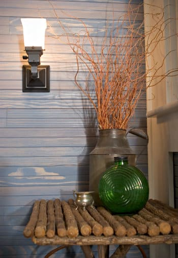 Tin milk can full of branches sits on a rustic log table with a green glass vase and a small silver ornament.