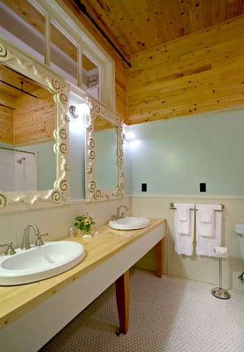Long wooden vanity with two sinks and mirrors with ornate wooden frames in a bathroomw ith a white tile floor.
