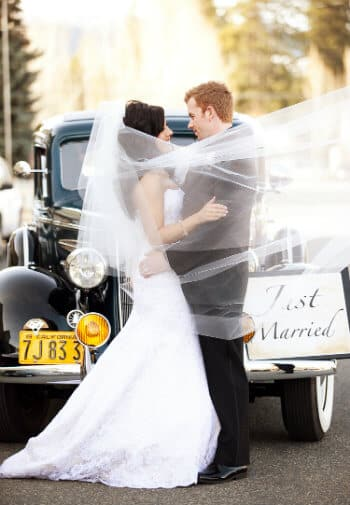 Bride in white gown embraces groom in front of a vintage car while her veil is blown around them romantically.