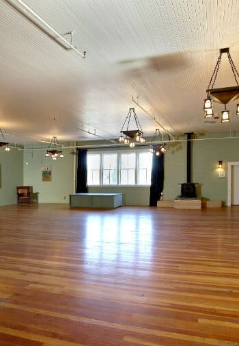 Large open event space with a wooden floor and lots of lighting.