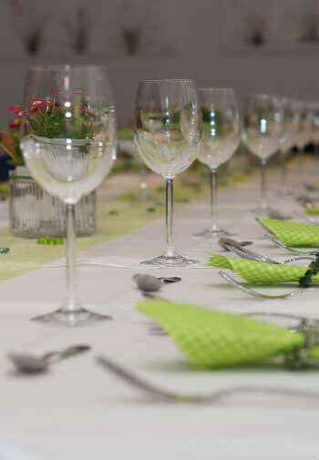 Table set with wine goblets and silver with green gingham napkins.