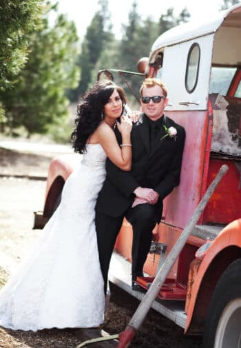 Bride in white gown and groom in black suit lean against a vintage red truck.