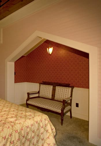 Sweet antique settee in a small alcove next to a bed in a bedroom decorated in pink and rose.