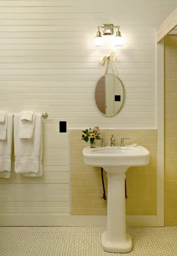 Bathroom with white paneling holds a pedestal sink and a rack with fluffy white towels.