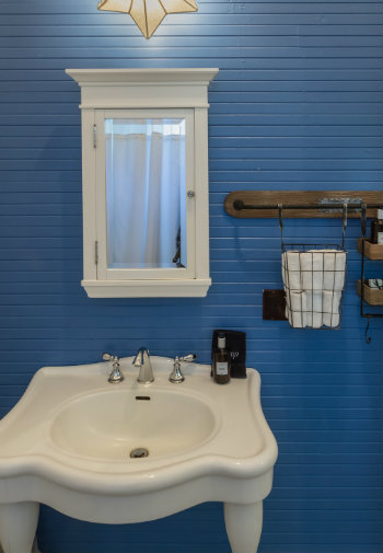 Freestanding white sink with white mirrored medicine cabniet in a bathroom with blue paneling.