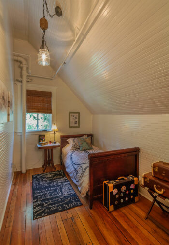 Cozy nook with pitched ceiling and a single bed made up with a bicycle spread.