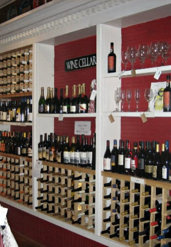 A wall of full wine racks and shelves with bottles of wine and champagne along with glasses.