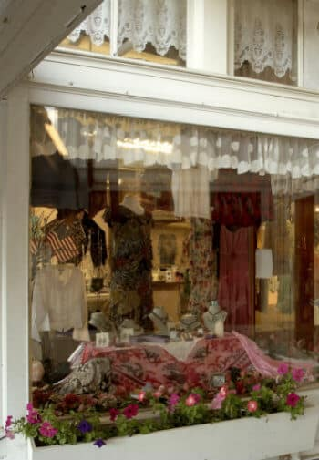 Front window of ladies clothing store, with lace curtains and a window box with pink pansies.