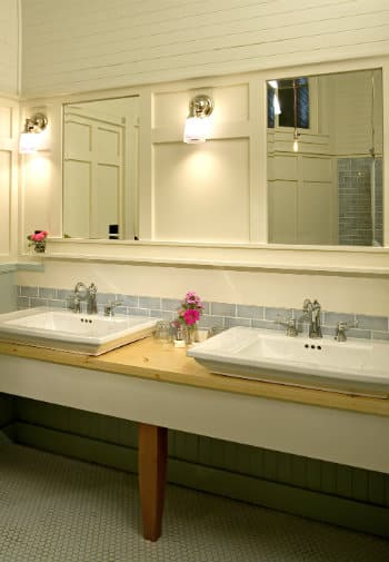 Two sinks inset into a wooden vanity under large mirrors with hanging lights.