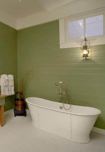 White metal soaking tub in a green paneled bathroom with a white penny-tile floor.