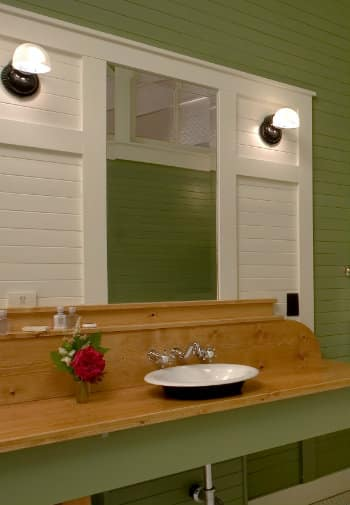 Enameled sink set into a long counter made of wood in a bathroom paneled in green and white.