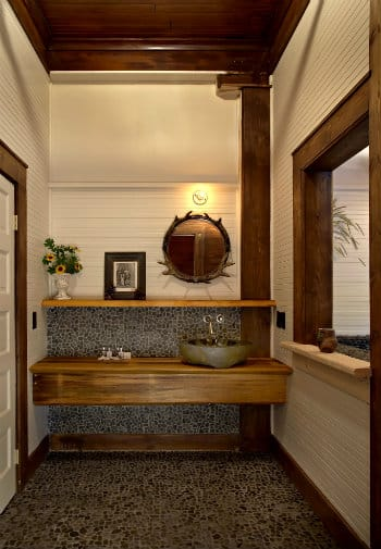 Unique wooden vanity with stone bowl sink and mirror framed in antlers.