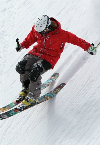 A skiier in a red coat and white helmet croches over skis precipitously balanced on a steep slope.