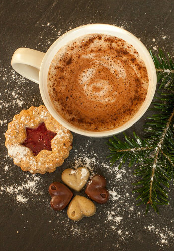 A white cup filled with cocoa on a tray with a cookie and chocolates dusted with powdered sugar.