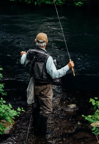 Older man in fly fishing gear casts off into a running stream.