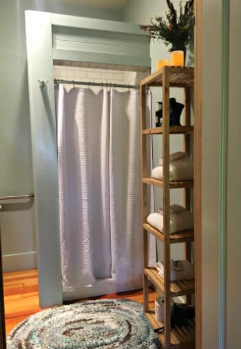 Bathroom with a shower and a rack holding white towels and toiletries.