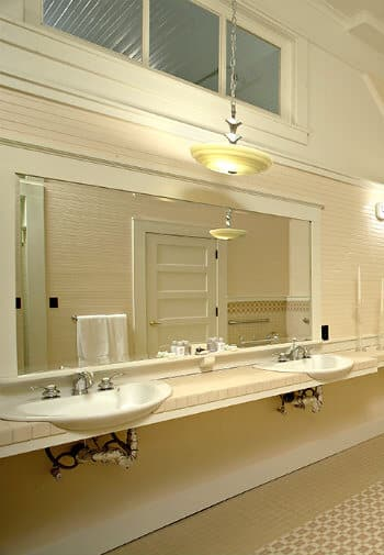 Large bathroom decorated in cream with multiple sinks along the wall.
